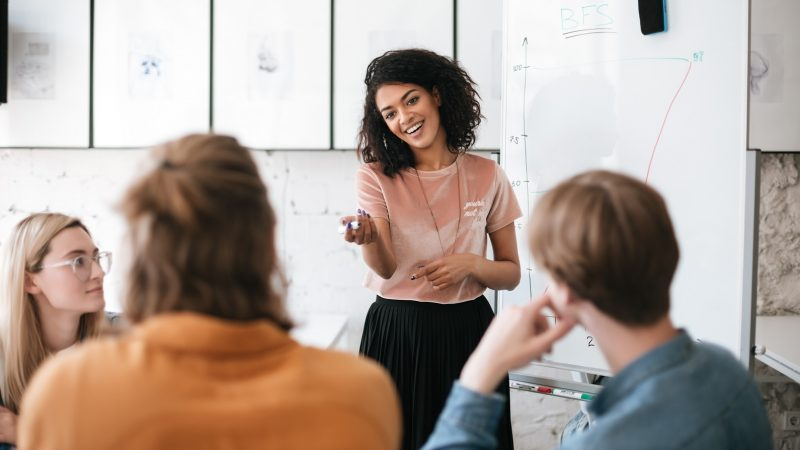 Beautiful African American lady with dark curly hair standing near board and happily looking at her colleagues in office. Young smiling business woman giving presentation to coworkers